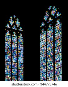 Stained glass windows against a silhouette church wall