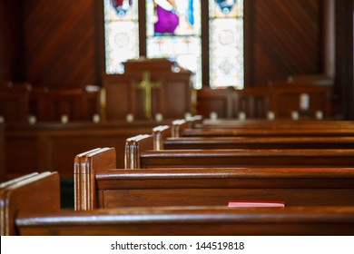 Stained glass windows in small church with wood pews