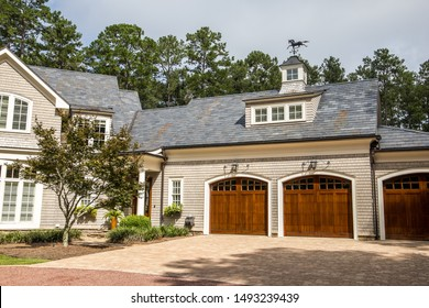 Stained wood custom triple garage doors for large southern home with curb appeal