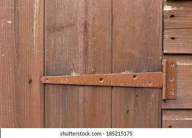 stained wooden door with painted metal hinge/bracket