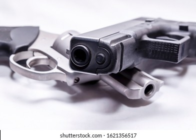 A stainless 357 magnum revolver with a black 9mm pistol on a white background