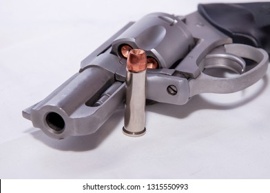 A stainless 357 magnum revolver with a single bullet next to it shown on a white background