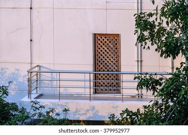 Stainless balcony and wooden door of apartment.