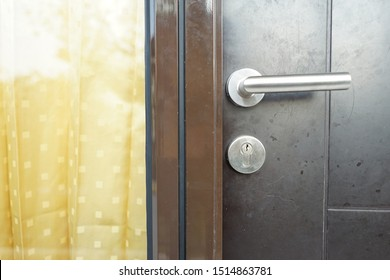 Stainless door knob or handle on brown door side by side with window and yellow curtains.
