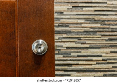 Stainless door knob and key hold on the wooden door and multicolor wall tile background.
