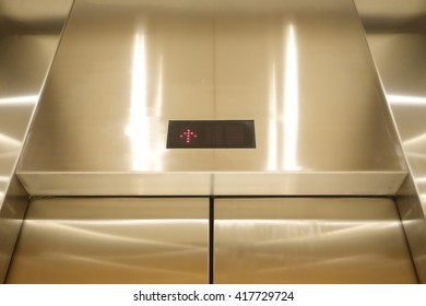 Stainless elevator or lift under yellow light.