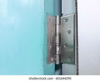 Stainless hinge on wooden green door.