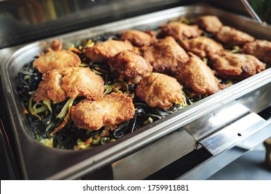 Stainless hotel pan on food warmer with fried meat and zucchini noodles. Self-service buffet table. Celebration, party, birthday or wedding concept. Image.