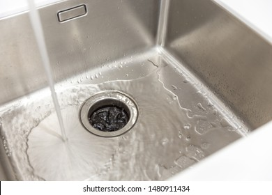 Stainless kitchen sink with food waste disposal in modern home