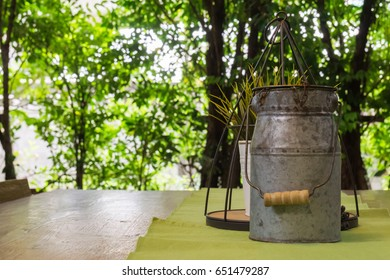 Stainless pot on wooden table with nature background