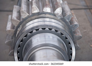 Stainless roller bearing on industrial size drive shaft. Shallow depth of field with only parts of the bearing in focus.
