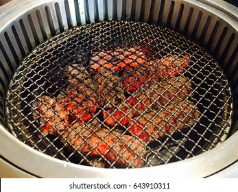 Stainless sieve with hot charcoal at Japanese bbq restaurant.