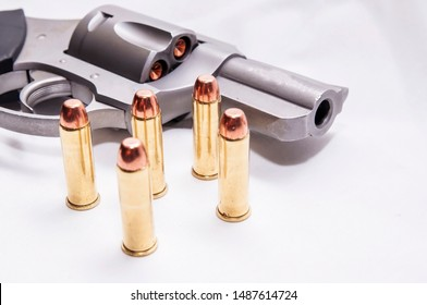 A stainless, snub nosed  357 magnum revolver with five full metal jacket bullets next to it on a white background
