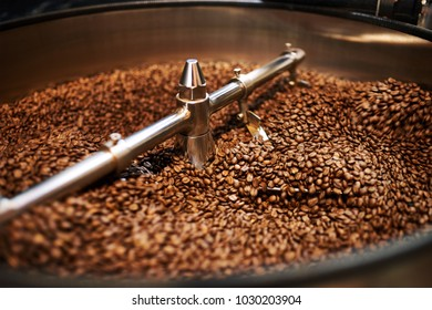 Stainless steel arms mixing freshly roasted coffee beans in large stainless steel cooling drum where the beans are cooled down before packaging or storing them.