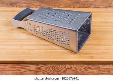 Stainless steel box-shaped four-sided kitchen grater lies on the wooden cutting board with large holes up and very fine grater forward