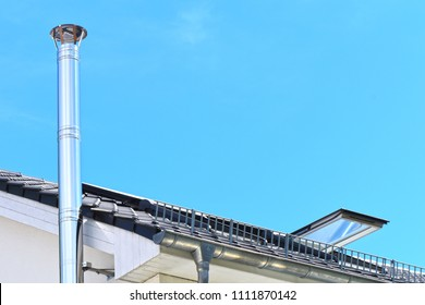 Stainless steel chimney and parts of a roof with an open roof window in front of a bright blue sky.
