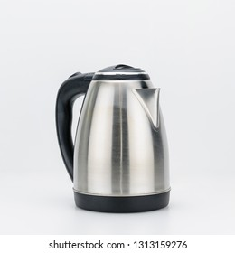 Stainless steel cordless electrical kettle with black plastic handle on white background.