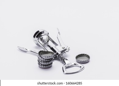 Stainless steel corkscrew wine bottle opener with metal lids beer bottle tops on white background with lots of copy space