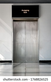 A stainless steel door of an elevator with refelcting tiles on the floor and a white wall.