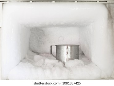Stainless steel drinking water glass in freezer of a refrigerator. Ice buildup inside of a freezer walls.