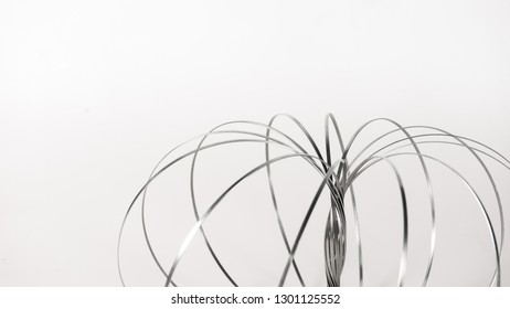 Stainless steel and elastic spring coil on empty background. Concept of business flexibility. Slightly de-focused and close-up shot. Copy space.