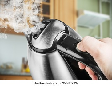 Stainless Steel Electric Kettle in hand on the background of the kitchen. focus on the lid of the kettle