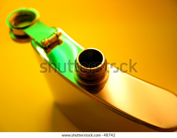 Stainless steel flask on a bright yellow background with a few highlights of green light. View from the top with the cover opened.