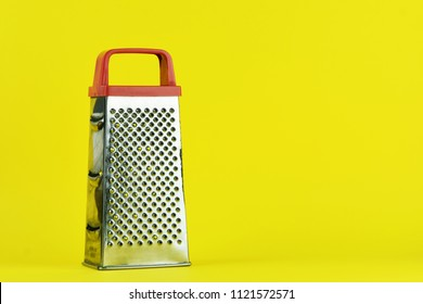 Stainless steel grater isolated. Kitchen accessories. Tools for cooking. Isolated on yellow background. For your design.