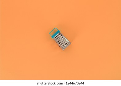 Stainless steel grater lies on a pastel colored paper. Kitchen accessories. Tools for cooking. Flat lay top view