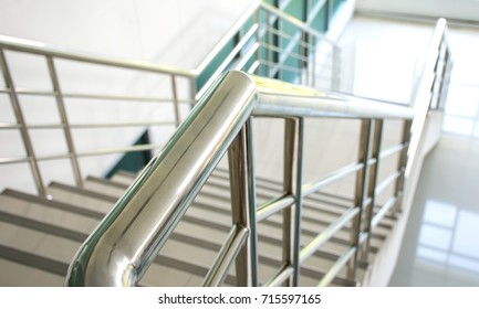 Stainless steel handrail and white stair in office building