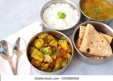 Stainless steel Lunch Box or Tiffin with Indian food menu Chapati or Roti, Garlic Dal Tadka, White Rice and Potato or Jeera aloo. with spoons, tissue paper and glass of water. Copy space