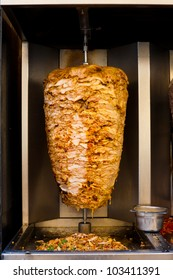 A stainless steel machine slowly grills skewered layers of succulent chicken with fat on top, a typical meat served inside a kebab sandwich in the Middle East