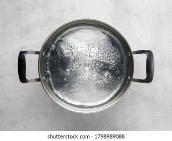 Stainless steel metal cooking pot of boiling water on gray concrete background , top view.