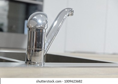 Stainless Steel Mixer Taps on sink and wooden worktop