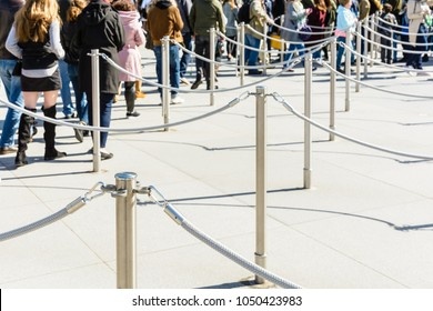 Stainless steel poles linked by grey ropes for queue control at the entrance of a tourist site, with drop shadows on a light ground and blurry people queueing up in the background.