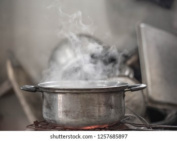 Stainless steel pot boiling water with white smoke in countryside kitchen.