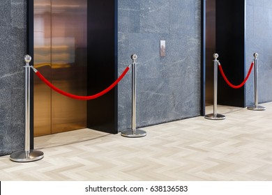 Stainless steel queue stand with red velvet rope barrier in front of elevator door