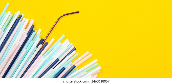 Stainless steel reusable drinking straw with many multicolored plastic straws on yellow background