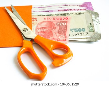 The stainless steel scissors with orange plastic handles is on top of the orange envelope which contain Indian Rupees on the white background
