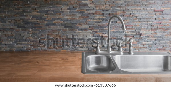 stainless steel sink and wooden kitchen counter and stone backsplash background