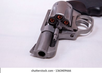 A stainless steel snub nosed 357 magnum revolver loaded with hollow point bullets on a white background