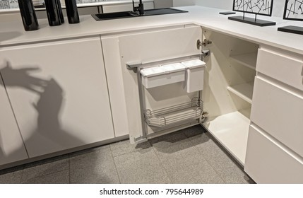 Stainless steel storage at the door inside white kitchen cabinet for accessories equipment.