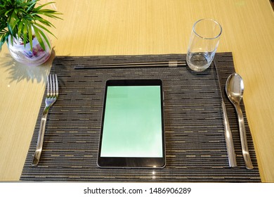 Stainless steel tableware and tablet computer in the kitchen table