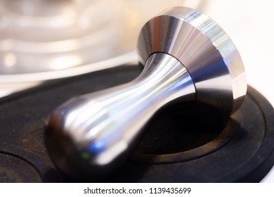 stainless steel tamper.barista equipment.heavy tamper for professional barista brew espresso coffee.close up tamper in coffee shop with space.