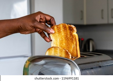 stainless steel toaster toaster with toasted bread for breakfast inside with kitchen in the background. Hands of Black Girl pulls out ready toasts.