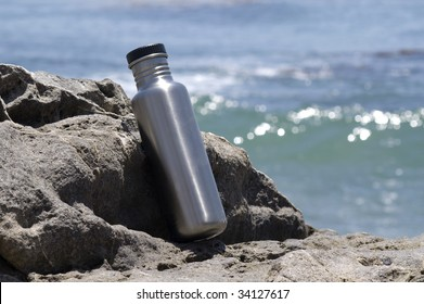 Stainless steel water bottle on a rock with the ocean in the background.