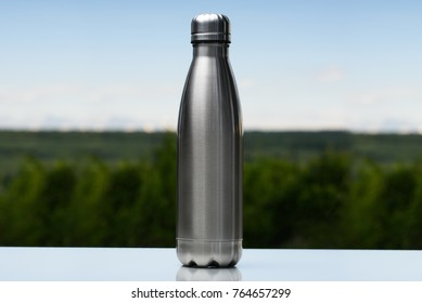 Stainless thermos, water bottle on the sky and forest background.