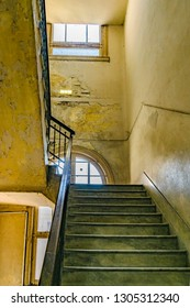 Stair and windows at neglected old building interior view