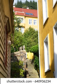 Staircase in Bergen surrounded by yellow houses in a sunny summer day