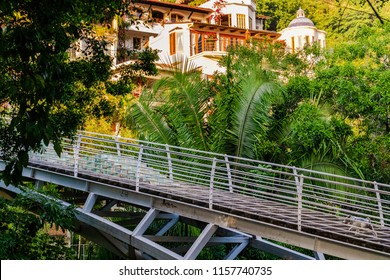 Staircase bridge leading from Isla Cuale across the Cuale River to Gringo Gultch in Puerto Vallarta Mexico with jungle environment and house in background.
